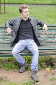 Handsome blond young man sitting on park bench — 图库照片