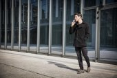 Young man smoking outside in urban setting — 图库照片