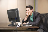 Preoccupied, worried young man staring at computer — Stock Photo