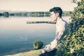 Handsome young man on a lake in sunny — Stock Photo