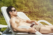 Shirtless Young Man Sunbathing in Lounge Chair on Grass — Stock Photo