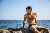 Young shirtless athletic man crouching in water by ocean shore — Stock Photo