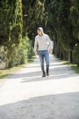Handsome young man walking along rural road — Stock Photo