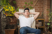 Handsome young man in balcony day-dreaming, sitting on chair — Stock Photo