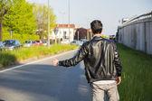 Задняя часть молодого человека, автостопом, ожидание на обочине дороги — Стоковое фото