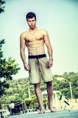 Young shirtless athletic man standing at the beach — Stock Photo
