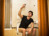Smiling young man taking selfie while defecating — Stock Photo