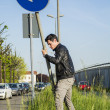 Young Man with Road Sign in Long Roadside Grass — Stock Photo #77716360