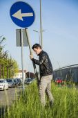 Young Man with Road Sign in Long Roadside Grass — Stock Photo