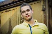 Handsome young man leaning against old train — Stock Photo