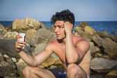 Shirtless Young Man Taking Selfie Photos at the Beach — Stock Photo
