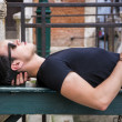 Attractive young man laying down on wood bench — Stock Photo #78846536