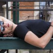 Attractive young man laying down on wood bench — Stock Photo #78847340
