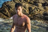 Giovane uomo atletico senza camicia in piedi in acqua da puntello dell'oceano — Foto Stock