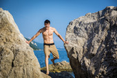 Young Man Spanning Gap Between Coastal Boulders — Stock Photo