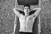 Shirtless Young Man Sunbathing in Lounge Chair on Beach — Stock Photo