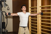 Attractive young man working out with dumbbells at gym — Stock Photo