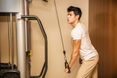 Joven guapo trabajando en equipos de gimnasio — Foto de Stock
