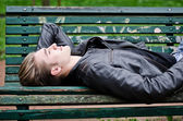 Attractive blue eyed, blond young man laying on park bench — Stock Photo