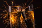 Clink glasses with fireworks background on new year's eve — Stock Photo
