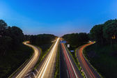 Highway crossing with lighttrails at sunset — Stock Photo