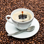 Cup of coffee with drop on beans — Stock Photo