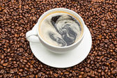Cup of coffee on beans — Stock Photo