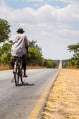 Místní muž, jízda na kole na pusté silnici — Stock fotografie