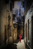 Veiled woman walking through a narrow street — Stock Photo