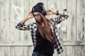 Girl in glasses, headphones and black beanie — Stockfoto
