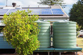 Water tank and solar panels — Stock Photo