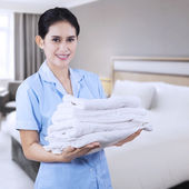 Pretty maid hotel with towels — Stock Photo