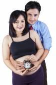 Happy family holding an alarm — Stock Photo