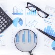 Magnifier with chart and calculator — Stock Photo #52830471