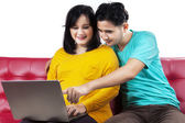 Pregnant lady and husband using laptop — Stock Photo