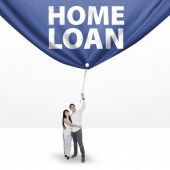 Couple pulling a home loan banner — Stock Photo
