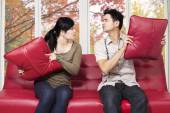 Couple quarreling and throwing pillow — Stock Photo