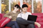 Couple using laptop at home in autumn — Stock Photo