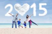 Family at beach under cloud of 2015 — Stock Photo