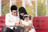 Family using digital tablet at home — Zdjęcie stockowe