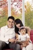 Family using digital tablet on sofa — Stock Photo