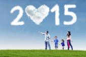 Happy family in field under cloud of 2015 — Stock Photo