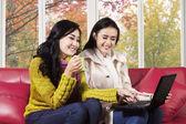 Joyful women using laptop on sofa — Stock Photo