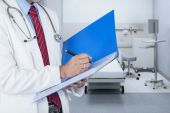 Doctor writing report on a folder  — Stock Photo