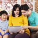 Hispanic family using digital tablet — Stock Photo