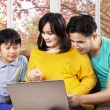 Hispanic family using laptop on sofa — ストック写真 #54736109