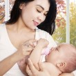 Hispanic mother feeding her child — Stock Photo #54736203