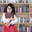 Schoolgirl with a book and apple in library — Stock Photo #54739057