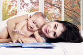 Asian mother and her baby girl on bed — Stock Photo