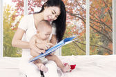 Baby read story book with mother — Stock Photo